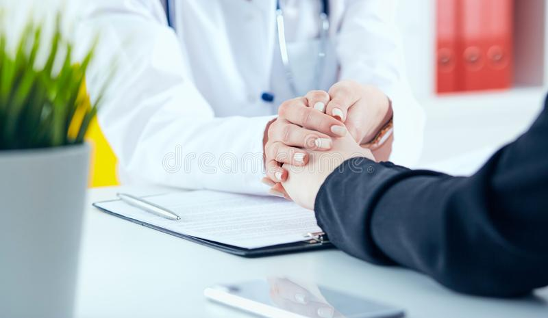 Friendly female doctor`s hands holding female patient`s hand for encouragement and empathy close-up. Partnership, trust. Friendly female doctor`s hands holding royalty free stock photos