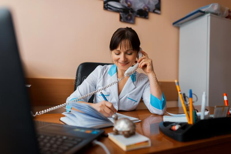 A friendly female doctor sits in her office and talks on the phone with one of the patients and writes something in a notebook. The doctor is working. The royalty free stock photo