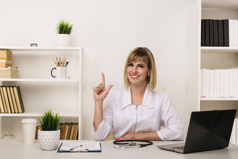 Friendly female doctor works at her desk in the office royalty free stock images