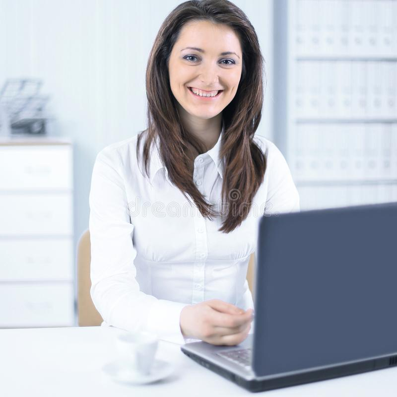 Friendly female employee sitting at her Desk. Photo with copy space stock photography