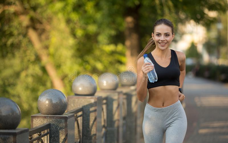 Friendly female jogger running in morning with water. Healthy sports lifestyle. Friendly female jogger running in morning with bottle of water, empty space royalty free stock photos