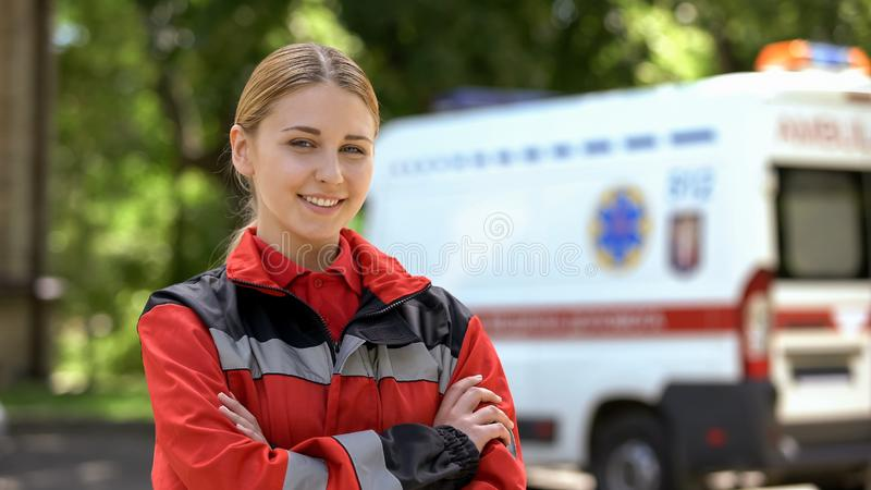 Friendly female paramedic posing for camera, ambulance on background, save lives. Stock photo royalty free stock photo