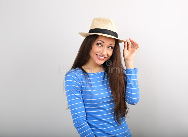 Friendly funny woman thinking in blue top and straw hat looking up royalty free stock photography
