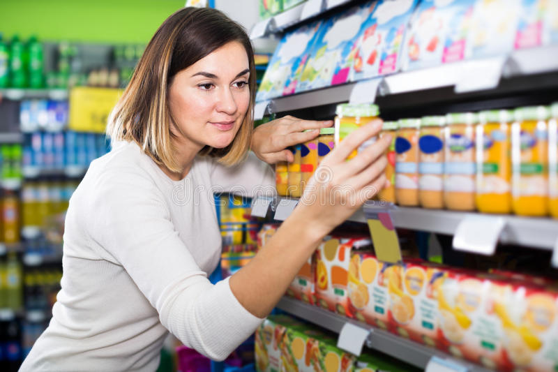 Friendly girl customer looking for tasty baby food stock image