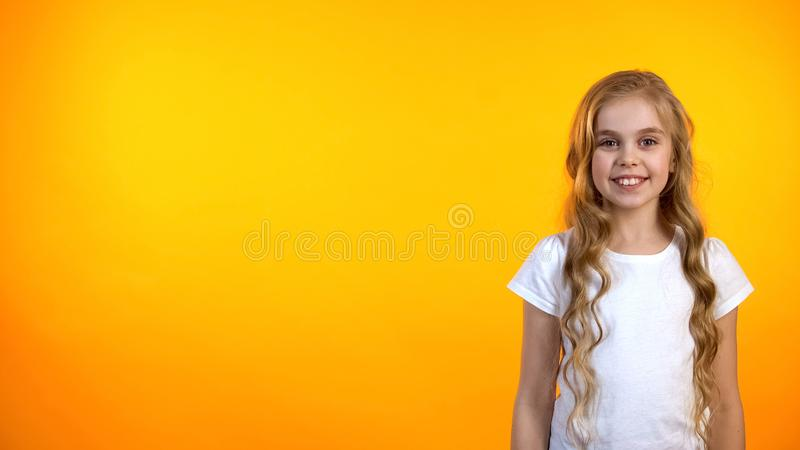 Friendly girl looking to cam and smiling isolated on orange background, template royalty free stock image