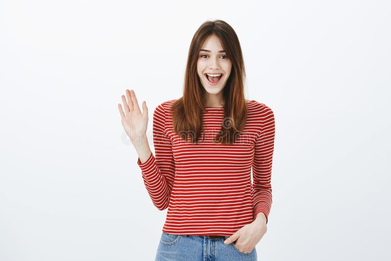 Friendly girl saying hi to best friends. Portrait of cheerful bright european woman in striped pullover, waving hand in royalty free stock photography