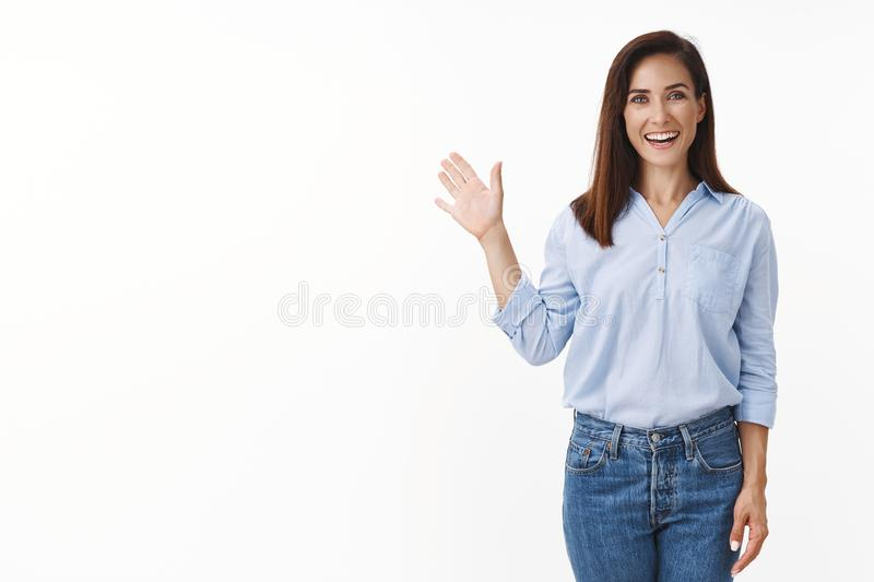 Friendly good-looking european woman entrepreneur with tattoo joyfully welcome you, wave palm gladly invite greet person. Smiling broadly, enthusiastic grin royalty free stock photography