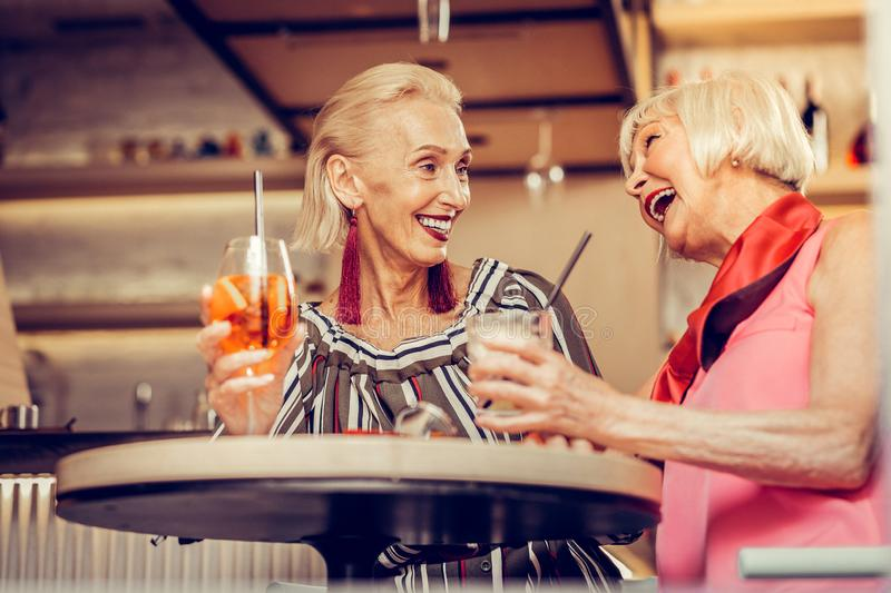 Friendly good-looking senior ladies actively communicating together. Partying in a bar. Friendly good-looking senior ladies actively communicating together while royalty free stock images