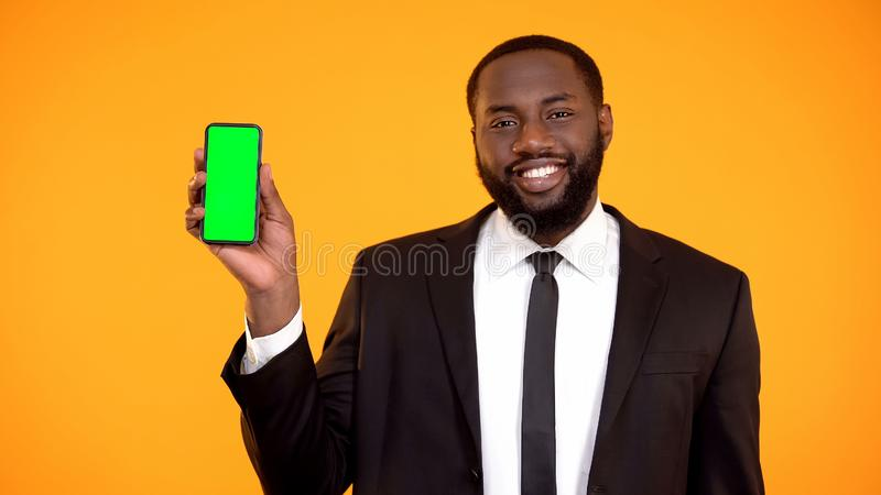 Friendly handsome afro-american man in suit showing prekeyed phone, template royalty free stock images
