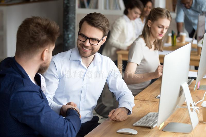 Friendly happy employee handshaking colleague at workplace thanking for help. Hr or team leader shaking hand of new worker welcoming coworker starting working stock photography