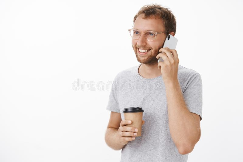 Friendly happy guy calling friend invite for morning coffee break in cafe holding smarpthone near ear and paper cup stock image