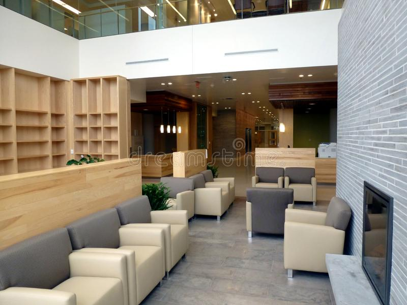 Friendly hospital interior waiting area with modern leather arm chairs and fire place stock photography
