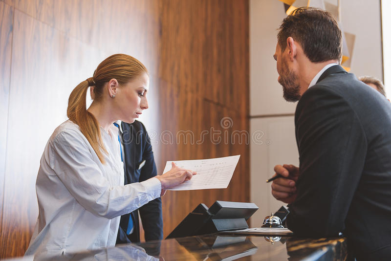 Friendly hotel worker at reception desk stock photo