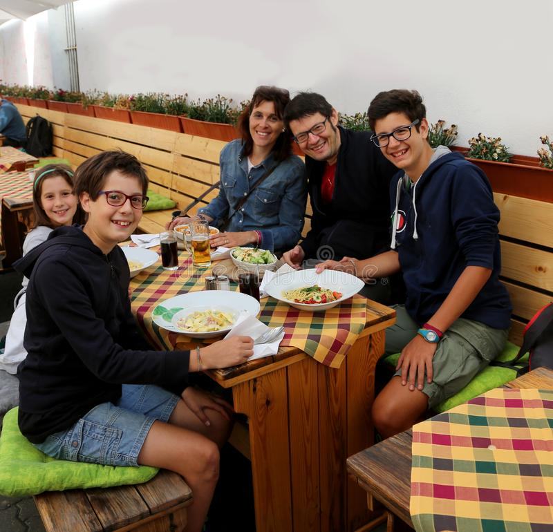 Friendly Italian family of five people during lunch in the resta stock photography