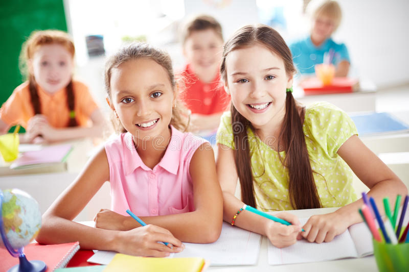 Friendly juniors. Cute schoolgirls looking at camera on background of other pupils stock image