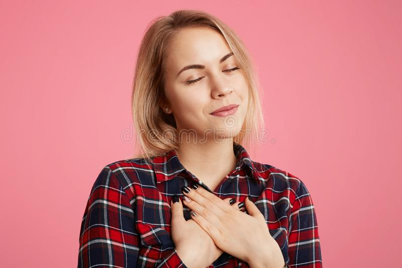 Friendly kind hearted female keeps eyes shut, hands on chest, expresses her gratitude to someone, poses against pink background. A stock images