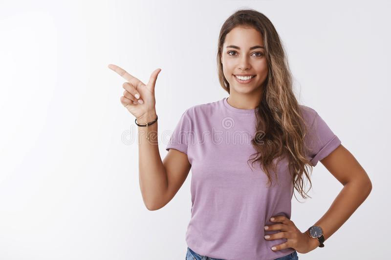 Friendly-looking cute happy smiling european girlfriend holding casually relaxed pose pointing left copy space stock photo