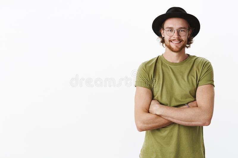 Friendly-looking delighted and calm handsome bearded male in glasses and hat smiling joyfully enjoying observing results royalty free stock image