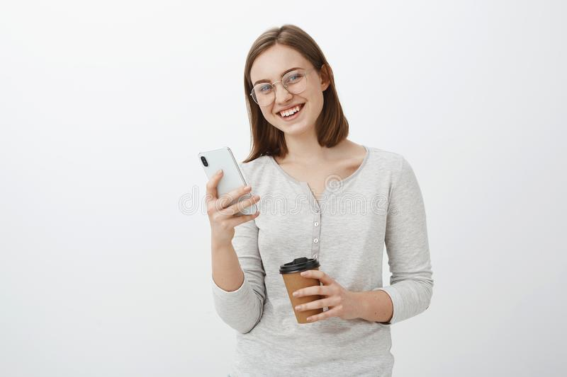 Friendly-looking enthusiastic caucasian girl in glasses with brown short hair holding smarpthone and paper cup of coffee. Waiting friend in cafe and playing in stock photo