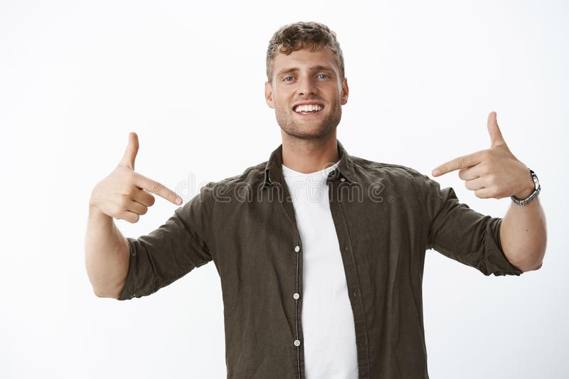 Friendly-looking joyful european blond guy with bristle pointing down using index fingers and smiling satisfied showing. Awesome advertisement, suggesting use royalty free stock photo
