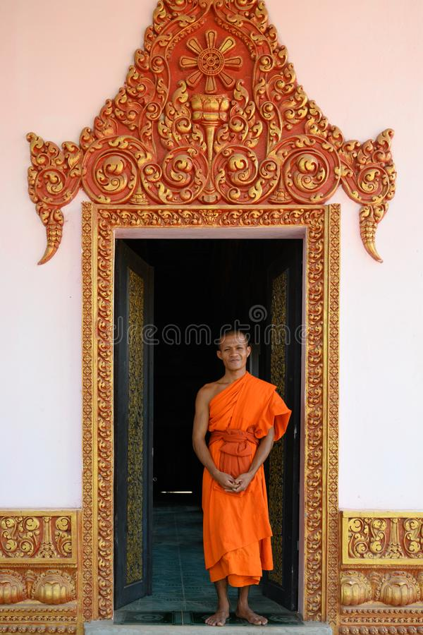 Buddhist monk in door with carved golden ornaments of monastery in Cambodia stock photography