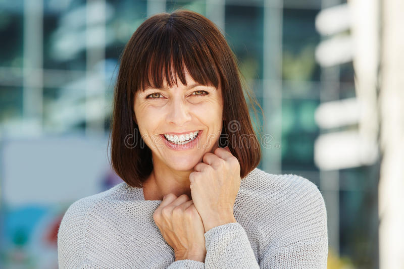 Friendly looking older woman holding sweater in cold weather royalty free stock image