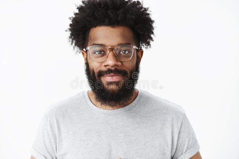 Friendly-looking outgoing and nice african american bearded male digital nomad in glasses with afro hairstyle smiling. With delighted and assertive expression stock image