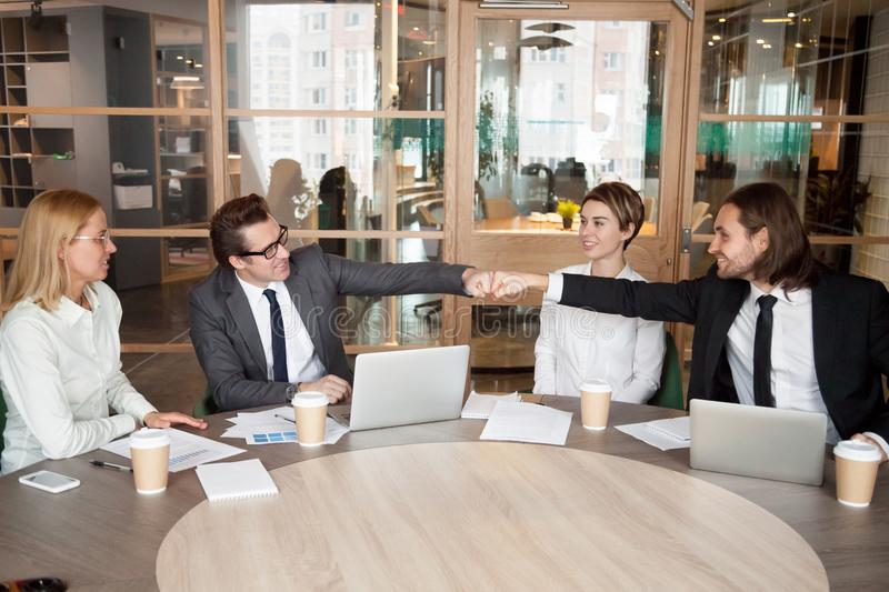 Friendly male colleagues or partners fist bumping at team meetin. G, happy smiling businessmen celebrate good teamwork result motivated by great collaboration stock images