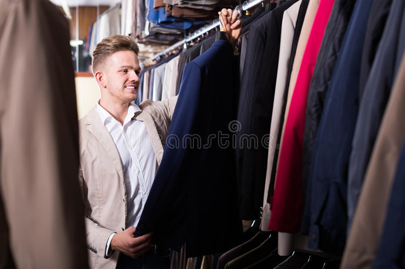 Download Friendly Male Customer Examining Men's Suits Stock Photo - Image: 83701370