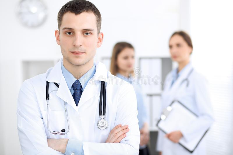 Friendly male doctor on the background of a female physician in hospital office stock photography