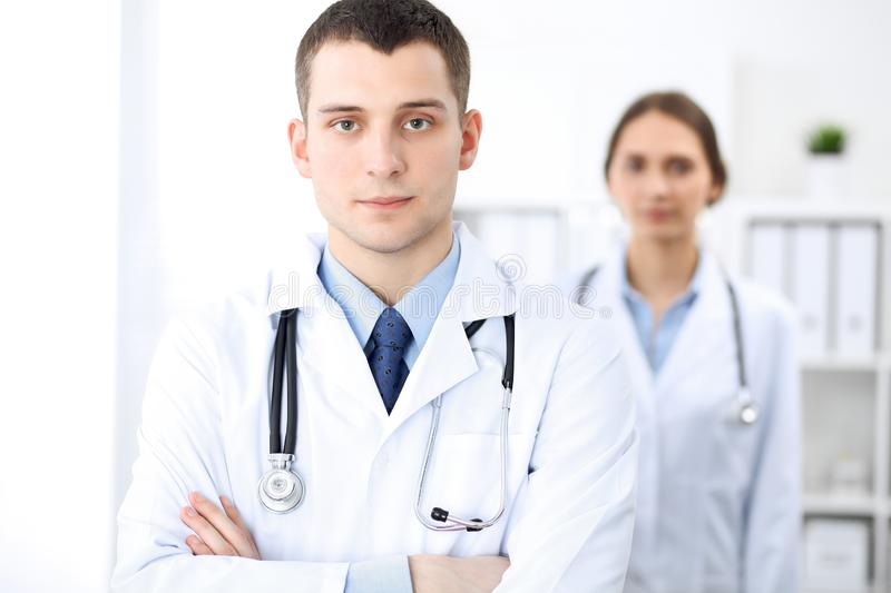 Friendly male doctor on the background of a female physician in hospital office royalty free stock image