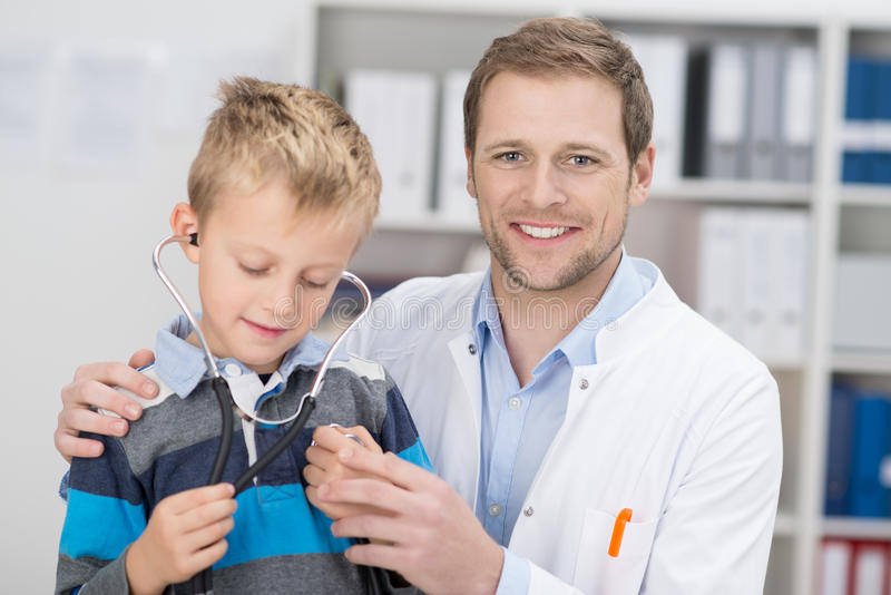 Friendly male doctor examining a young boy royalty free stock photos