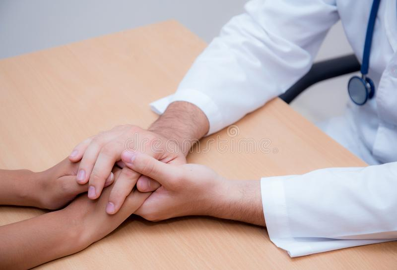 Friendly male doctor hand holding patient hand sitting at the desk for encouragement royalty free stock photos
