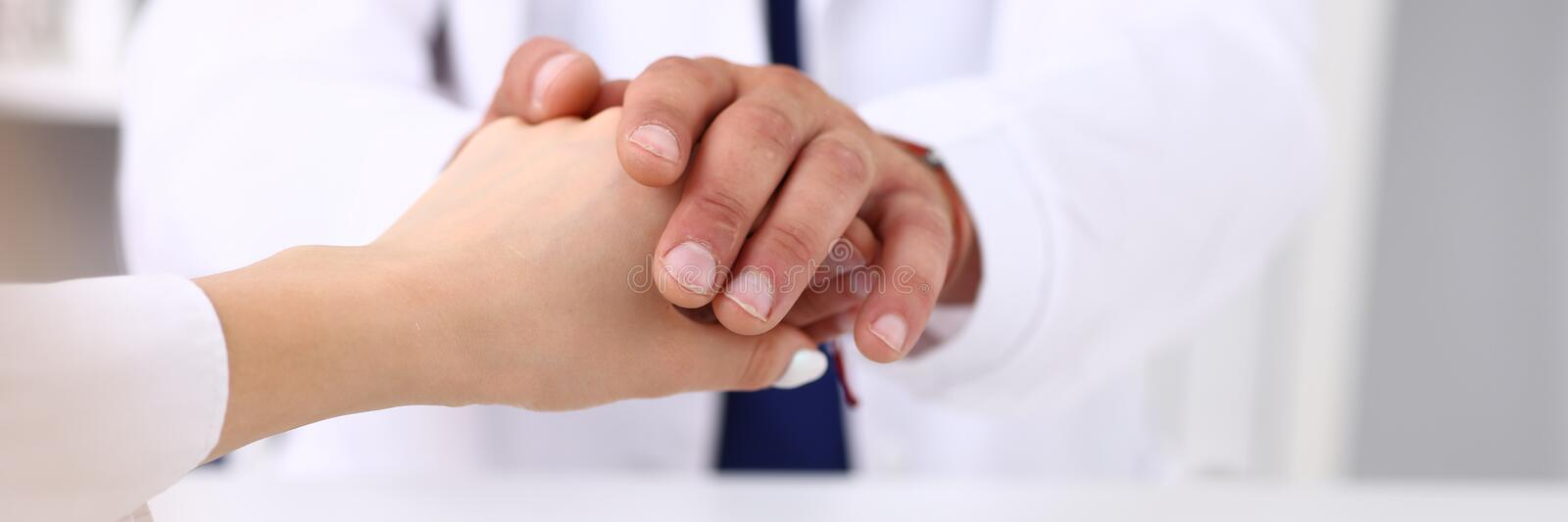 Friendly male doctor hold female arm in office during reception. Closeup. Examination result, positive test, calm down, promise and cheer up, grief and suffer royalty free stock photos