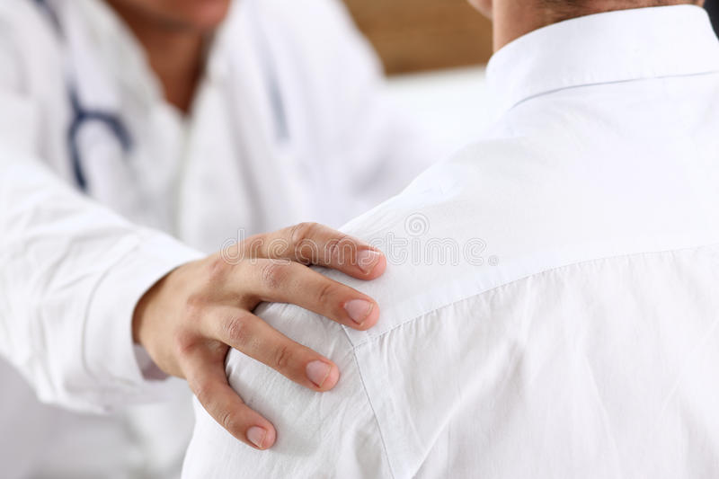 Friendly male doctor hold patient shoulder in office during reception. Examination result, positive test, calm down, promise and cheer up, grief and suffer stock photography