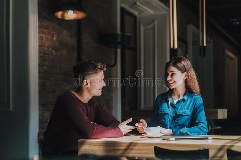Friendly male and female colleagues discuss work stock photography