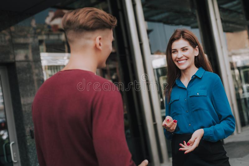 Friendly male and female colleagues meet on street stock image