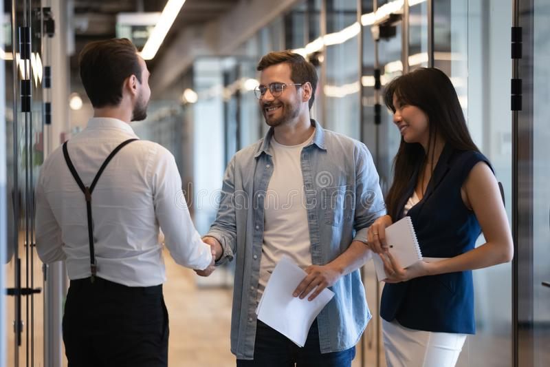 Friendly male professional colleagues greeting handshaking meeting in office hall. Friendly male professional colleagues greeting handshaking meeting in company stock photography