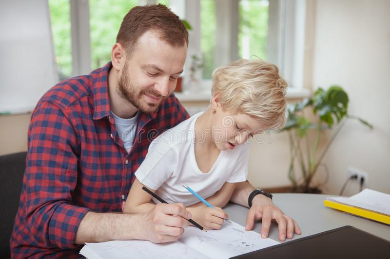Friendly male teacher helping his little student. Cheerful male teacher smiling joyfully, helping his little student drawing. Art class teacher sketching with stock image