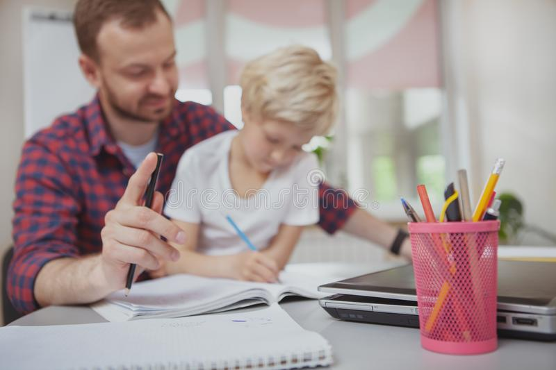 Friendly male teacher helping his little student. Selective focus on pens and pencils on foreground, little girl and her teacher drawing together on background royalty free stock image