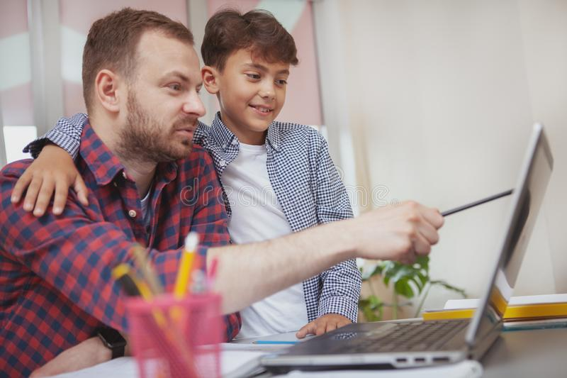 Friendly male teacher helping his little student royalty free stock images