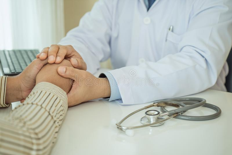 Friendly man doctor hands holding patient hand sitting at the desk for encouragement, empathy, cheering and support while medical stock photo