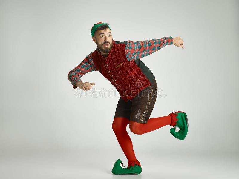 Friendly man dressed like a funny gnome posing on an gray background stock image