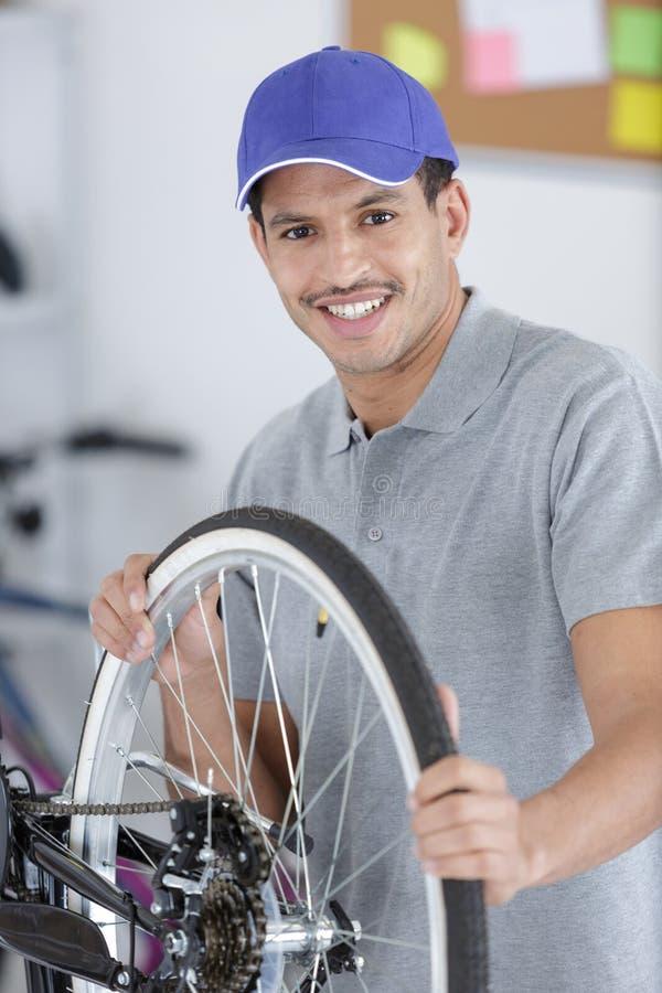 Friendly man working in bike workshop stock photo