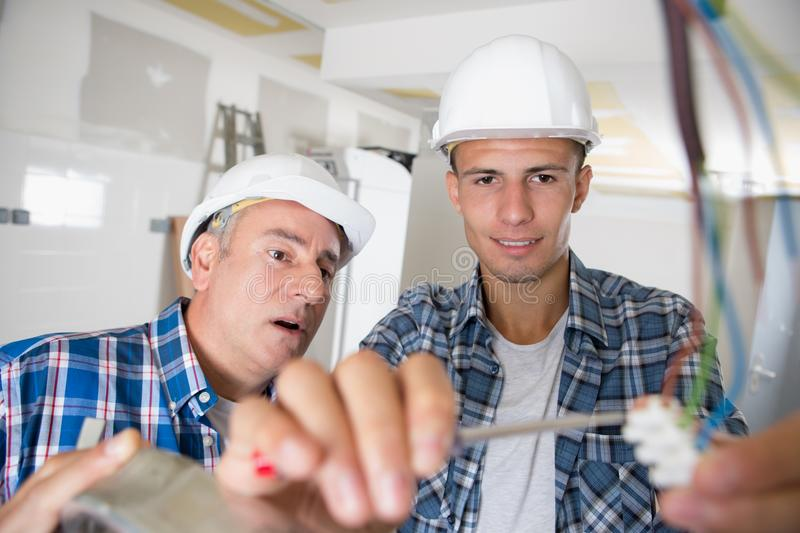 Friendly master electrician and apprentice working on breaker panel royalty free stock photography