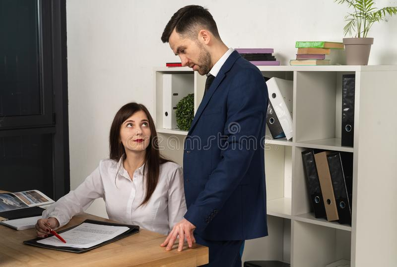 Friendly mentor explaining task for young employee royalty free stock photography
