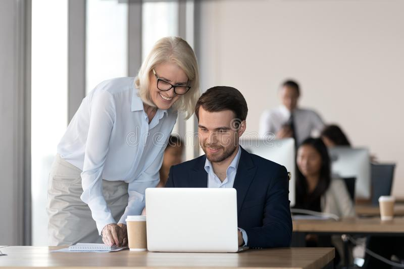 Friendly mentor training employee in office helping with computer work stock images