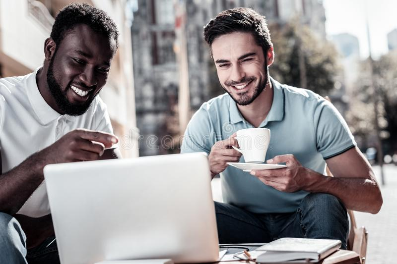 Friendly millennial colleagues discussing project in local cafe stock photo