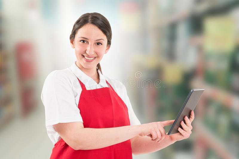 Friendly and modern hypermarket employee. Holding wireless tablet stock images