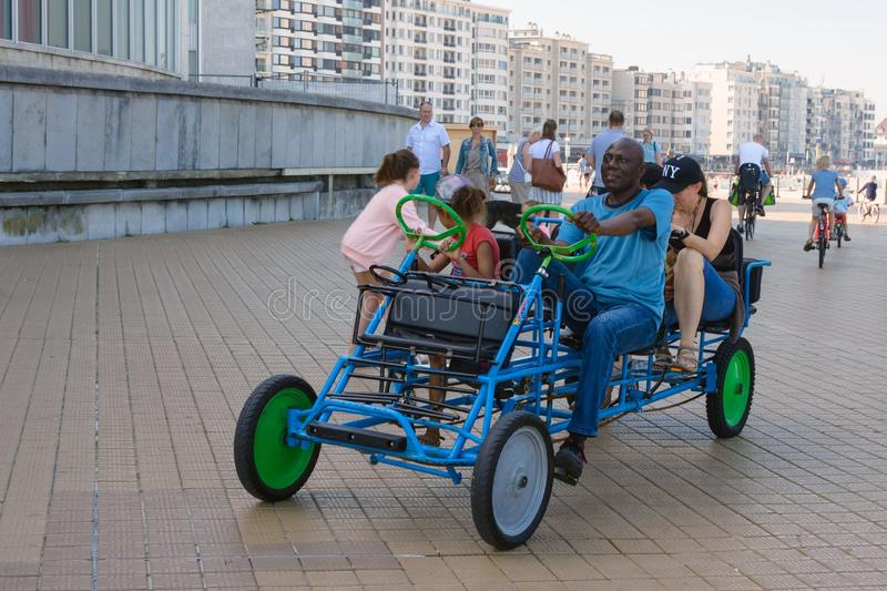 Friendly multi-ethnic family riding a blue multi-seat bicycle. The beautiful promenade of Ostend. A fun trip stock photography